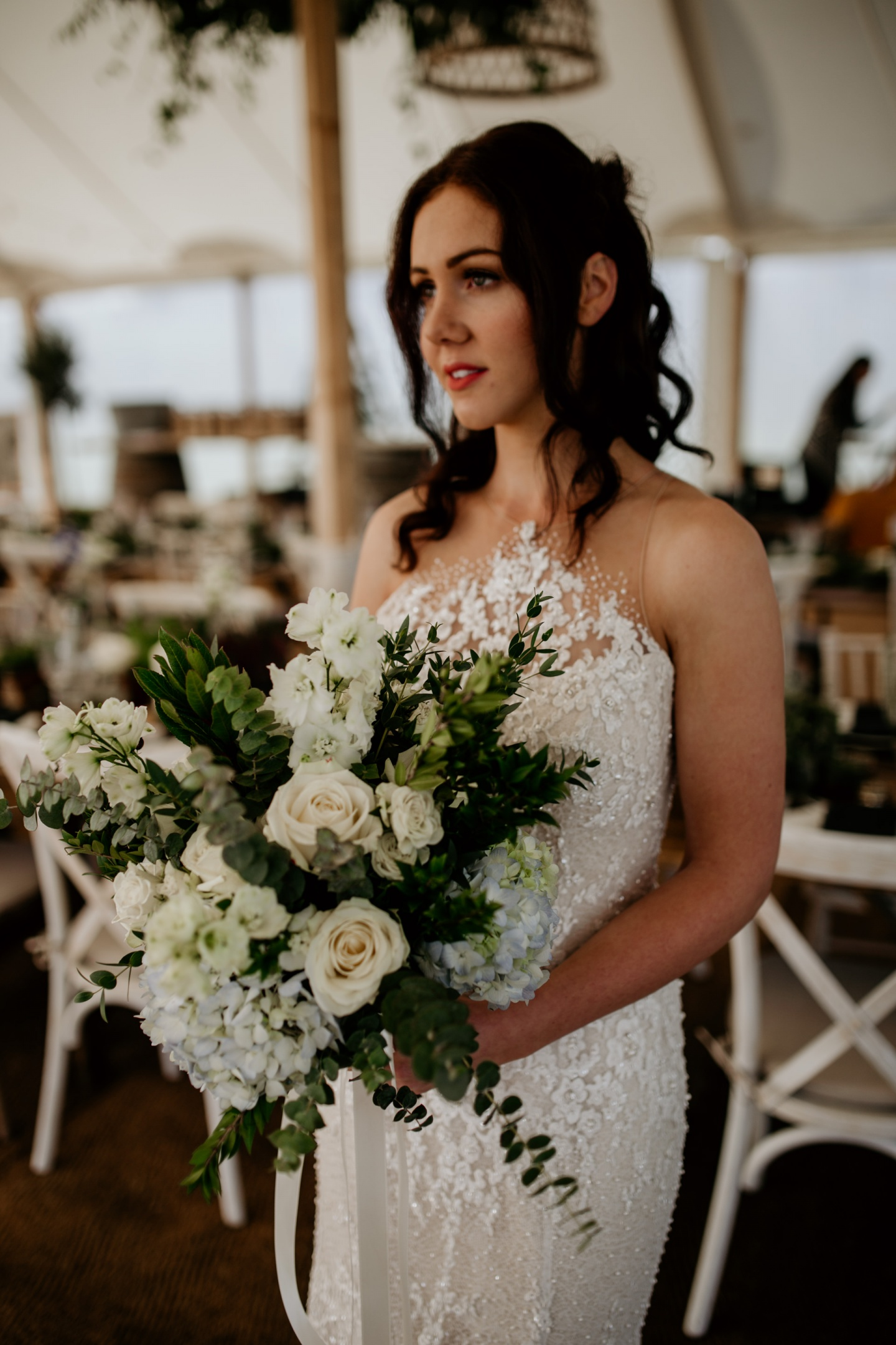 Bride standing in a marquee with white flowers